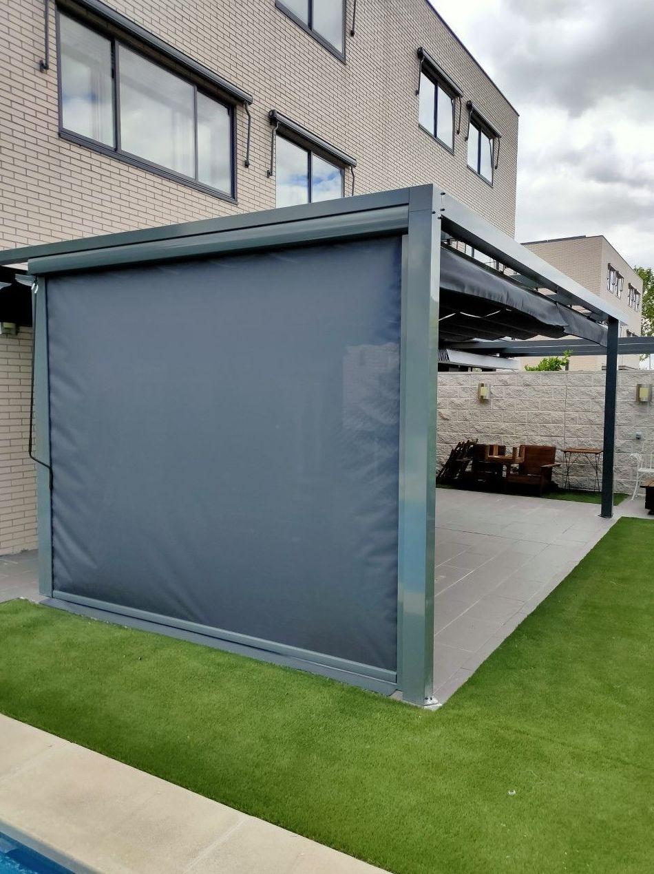 Toldo vertical instalado en el lateral de una pérgola y toldos Microbox en las ventanas