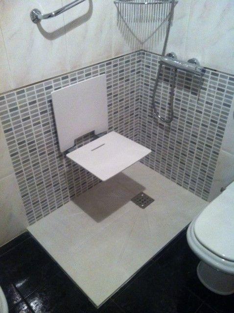 Plato de mármol técnico con azulejado y asiento de ducha plegable.