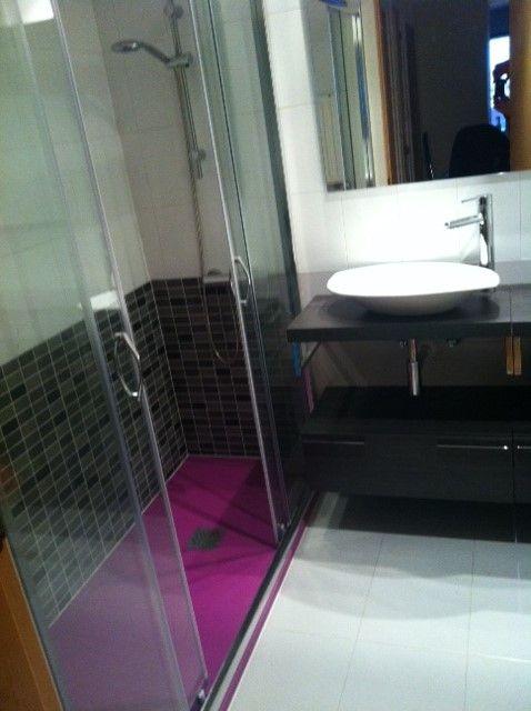 Plato de resina y azulejado. Mueble con lavabo sobre encimera.