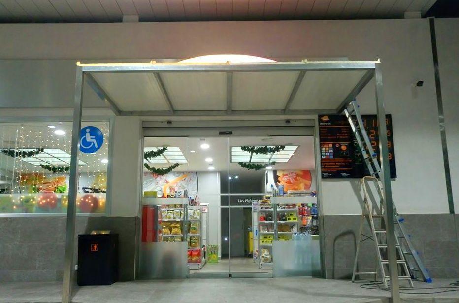 Marquesina de acero inoxidable montada en puerta de acceso de local comercial de área de servicios.