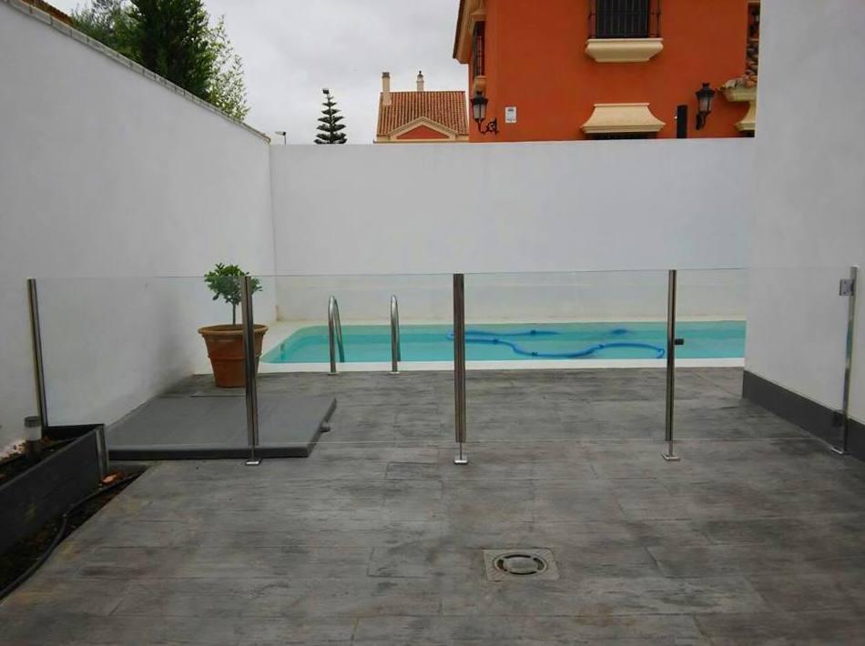 Barandilla de acero inoxidable y vidrio con puerta de acceso a piscina diseñada y fabricada a medida para vivienda particular