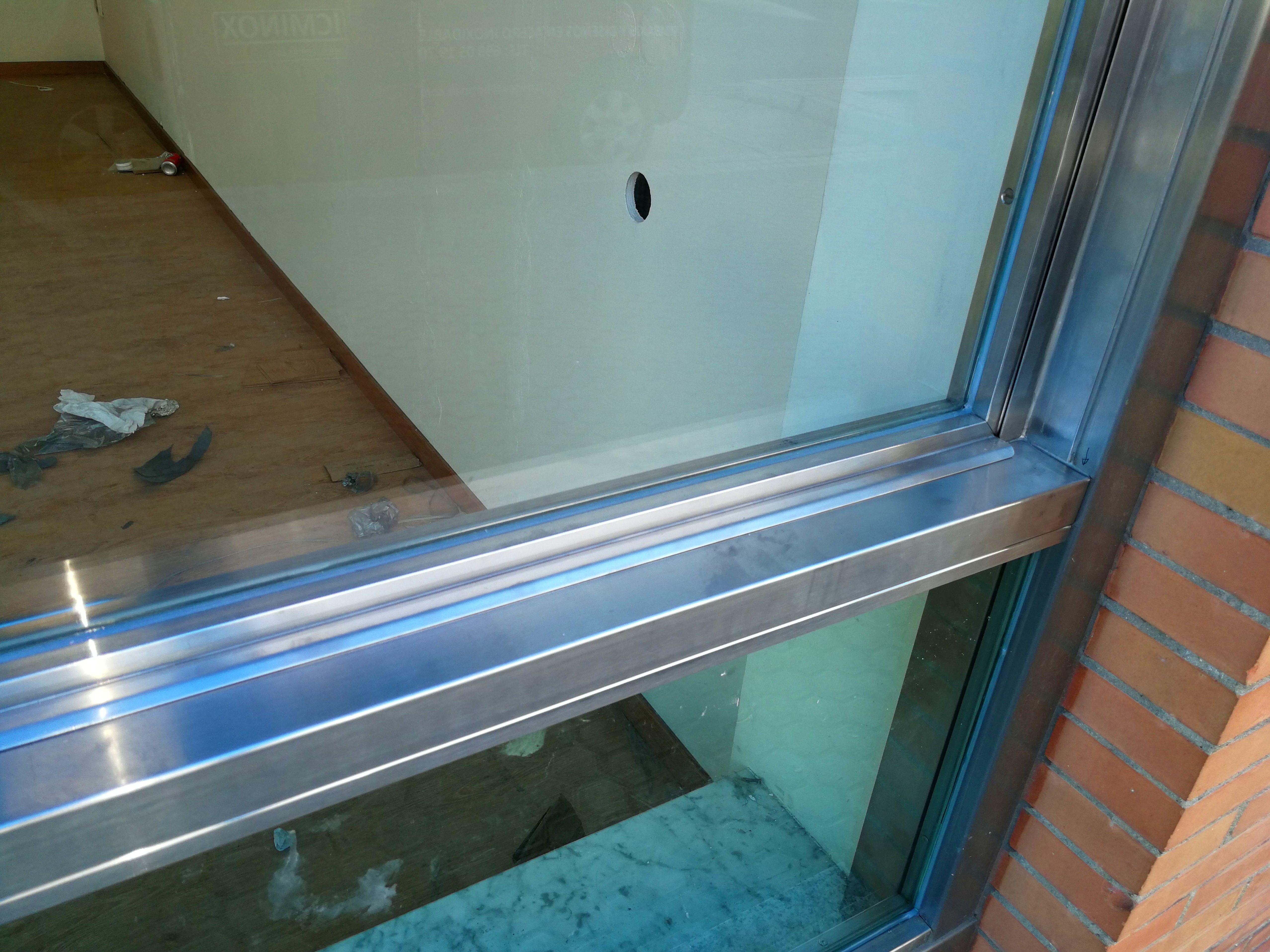 Ventana guillotina de acero inoxidable y vidrio montada en escaparate comercial