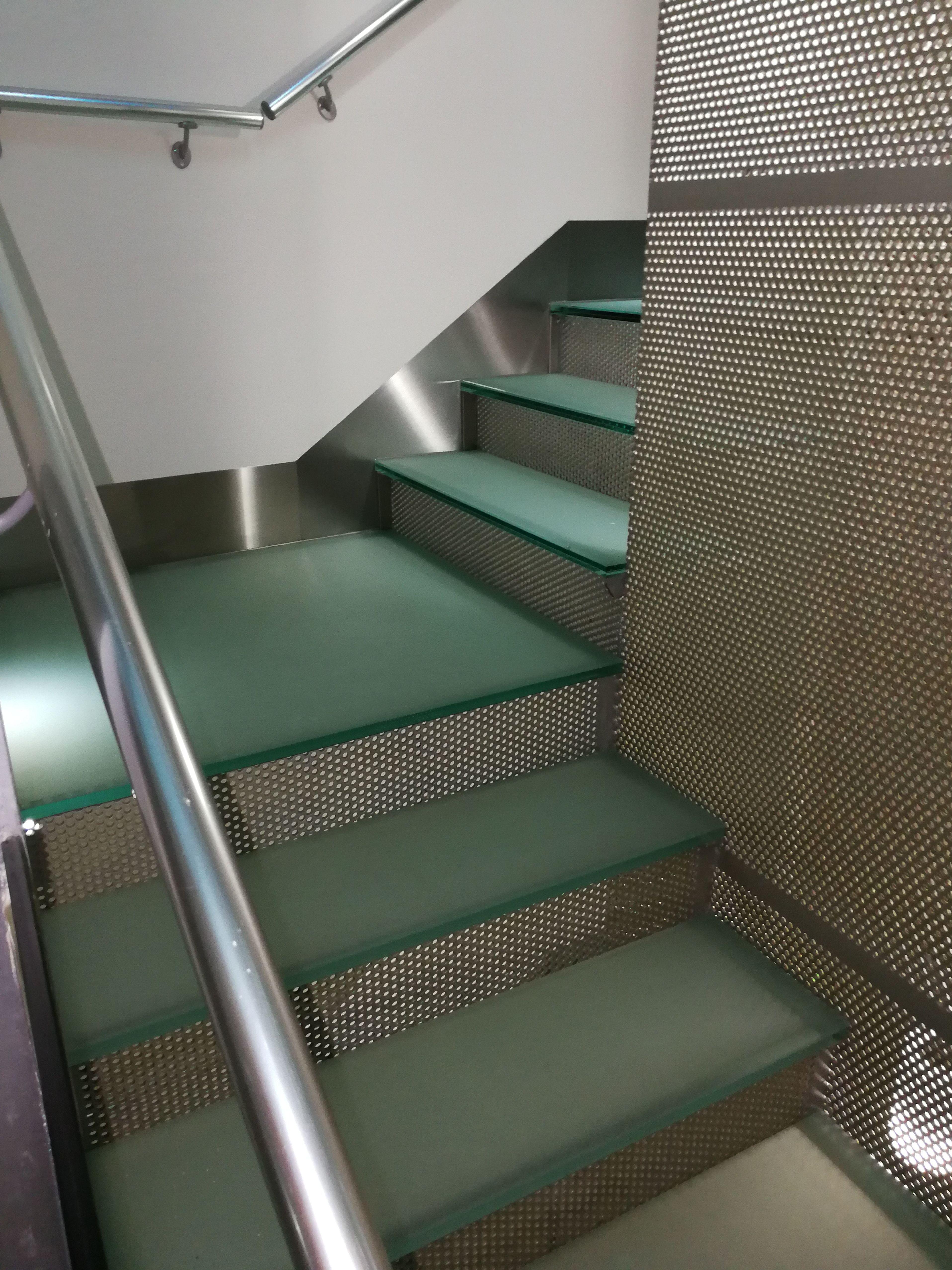 Zócalos de acero inoxidable en escalera de vidrio de hotel.