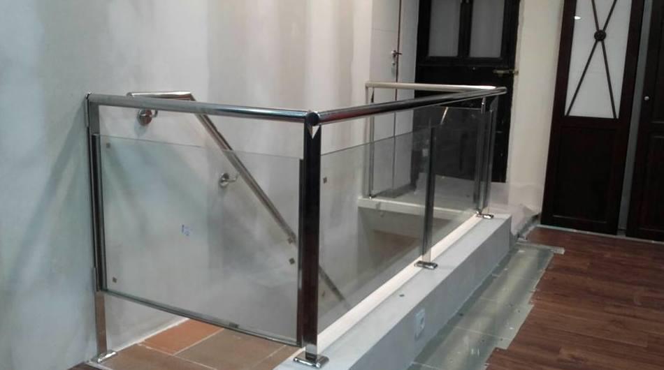 Barandilla de acero inoxidable y vidrio con puerta de acceso a sótano diseñado y montado a medida para local comercial.