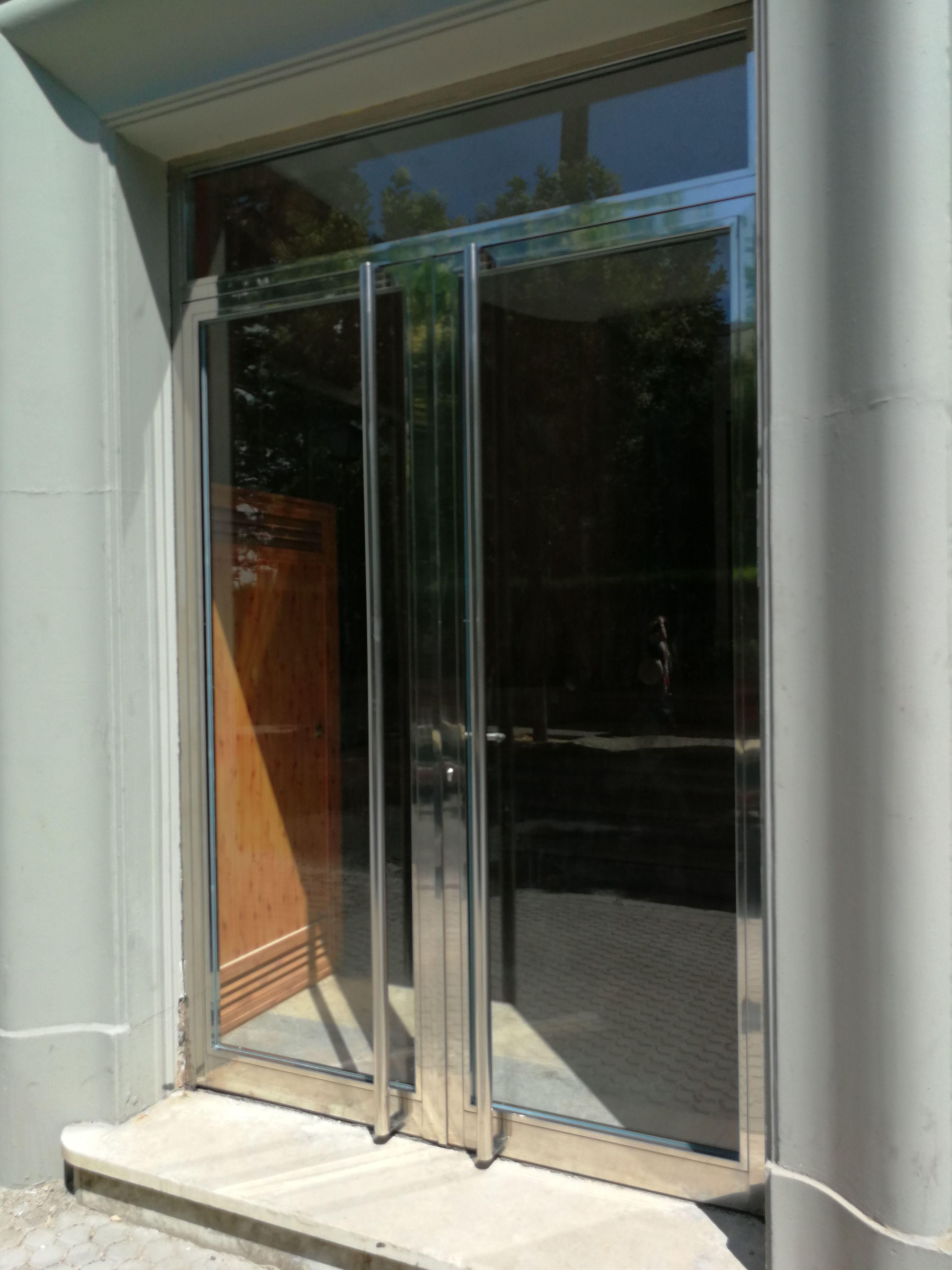 Puerta de acero inoxidable con vidrios de seguridad fabricada a medida.