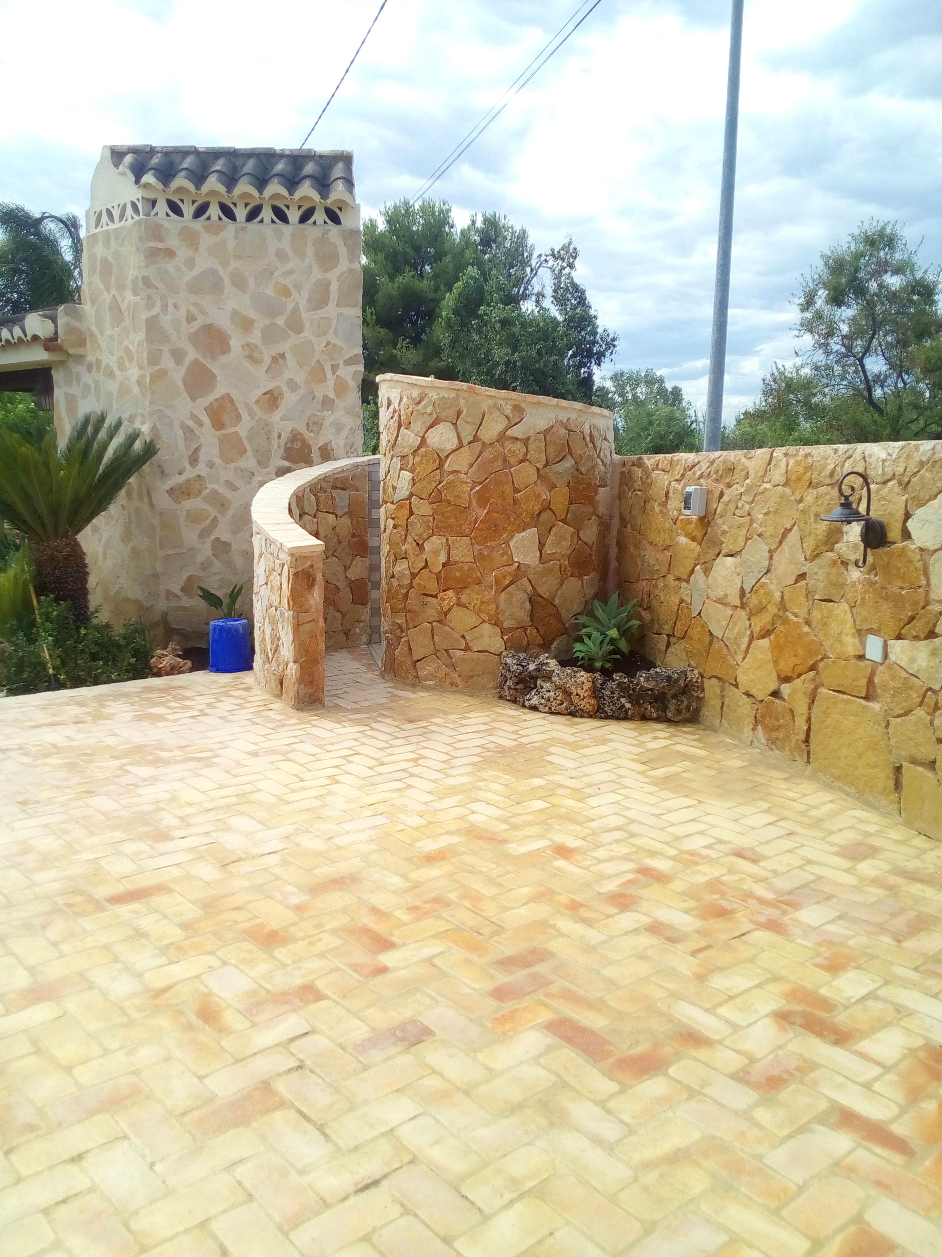 Terraza de piscina con ducha y revestimientos de piedra sin rejuntar