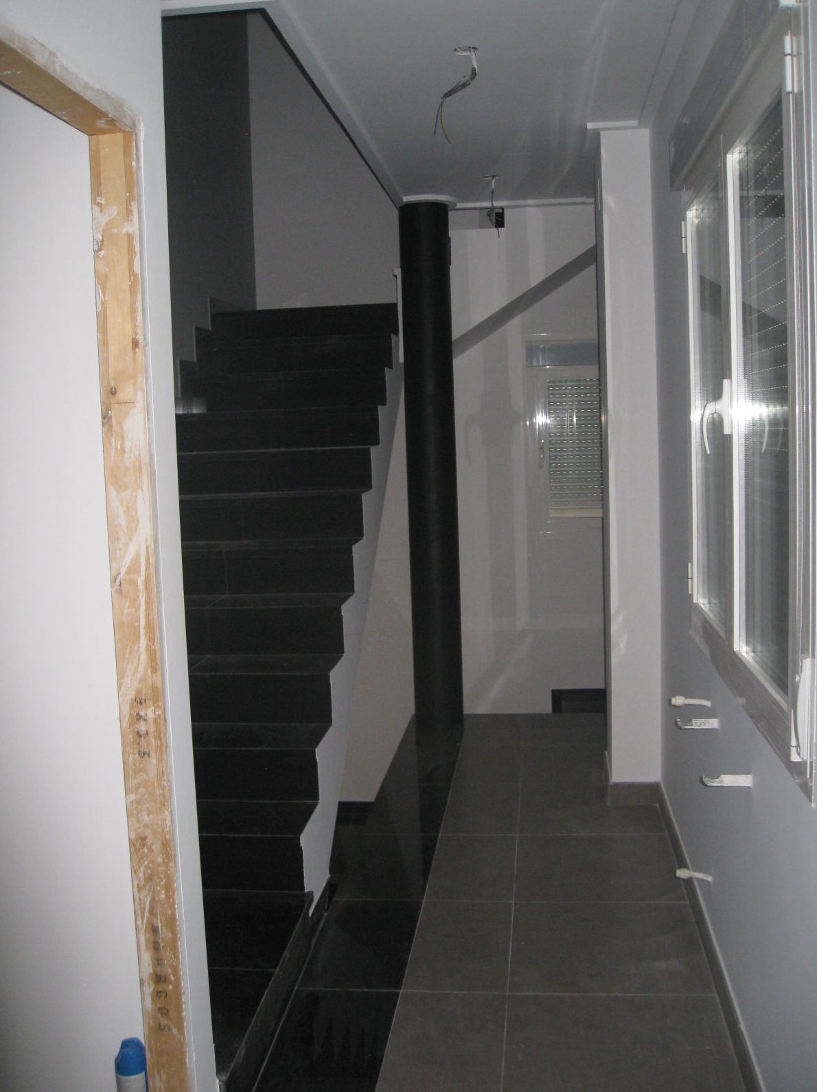 Acabado revestimiento de escaleras con gres porcelanico, en negro brillo