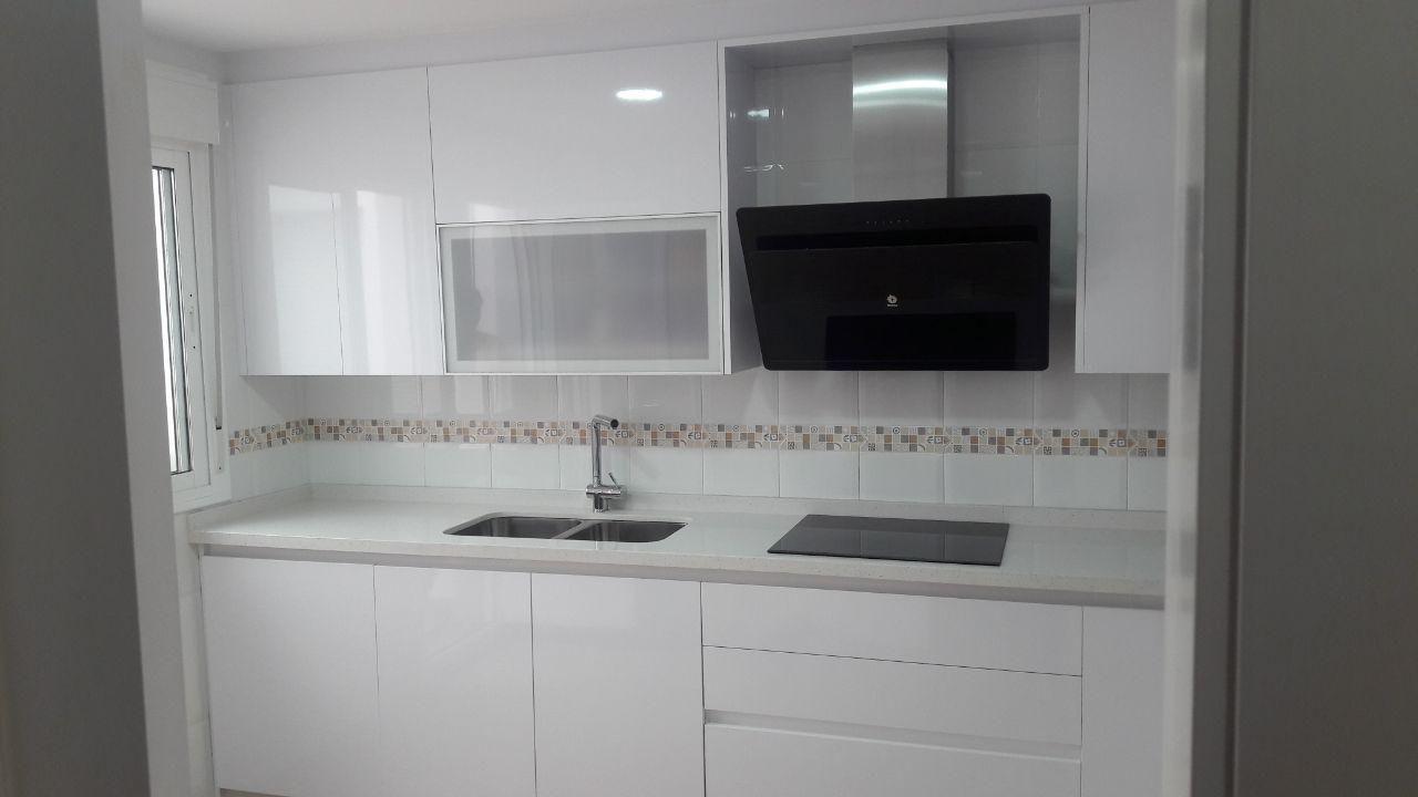 Cocina Gola en blanco brillo, con encimera Compac Moon, y electrodomésticos Balay...