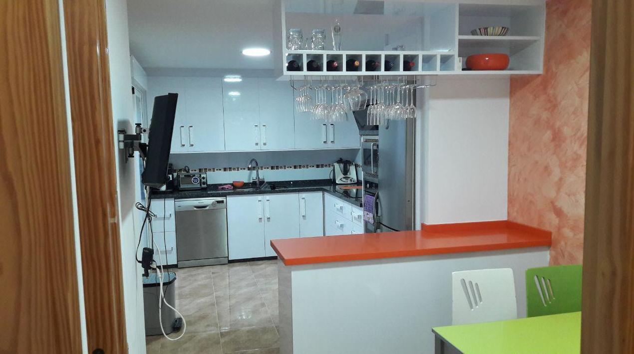 Cocina formica blanco brillo con encimera granito labrador claro, y peninsula silestone orange cool, con un mueble botellero y portacopas