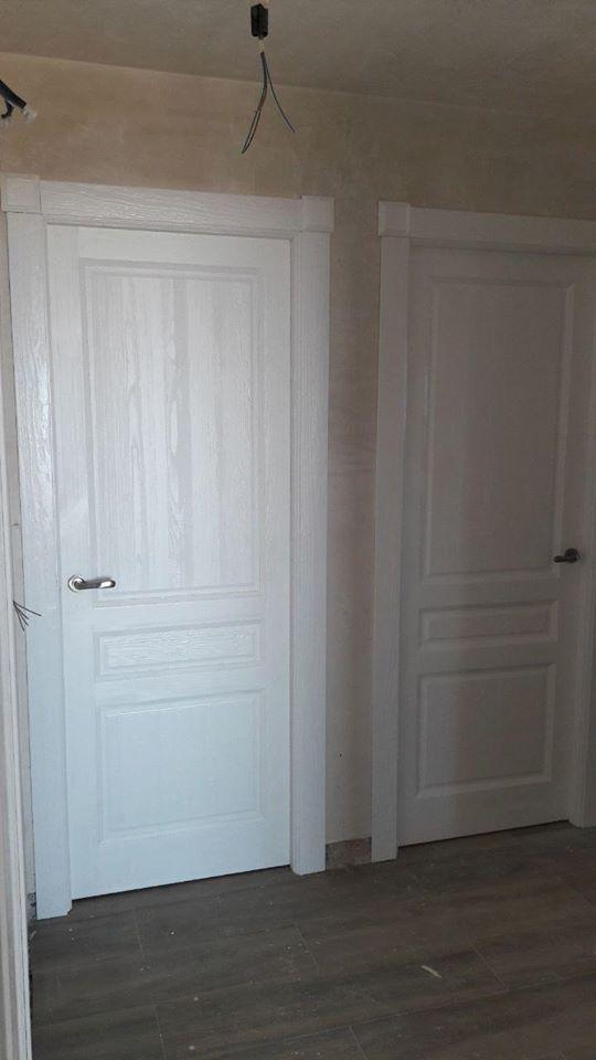 Puertas de paso plafonadas de madera maciza con la veta sacada, lacadas en blanco. una mezcla de estilos, moderno con rústico