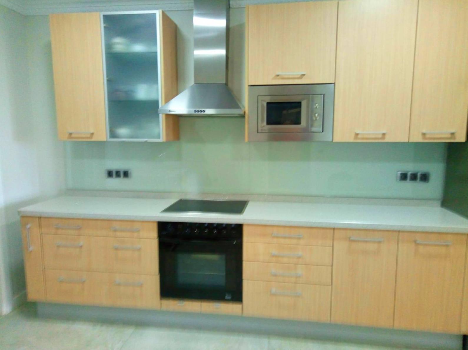 Frontal de cocina de cristal lacobel blanco roto con cajas para enchufes.