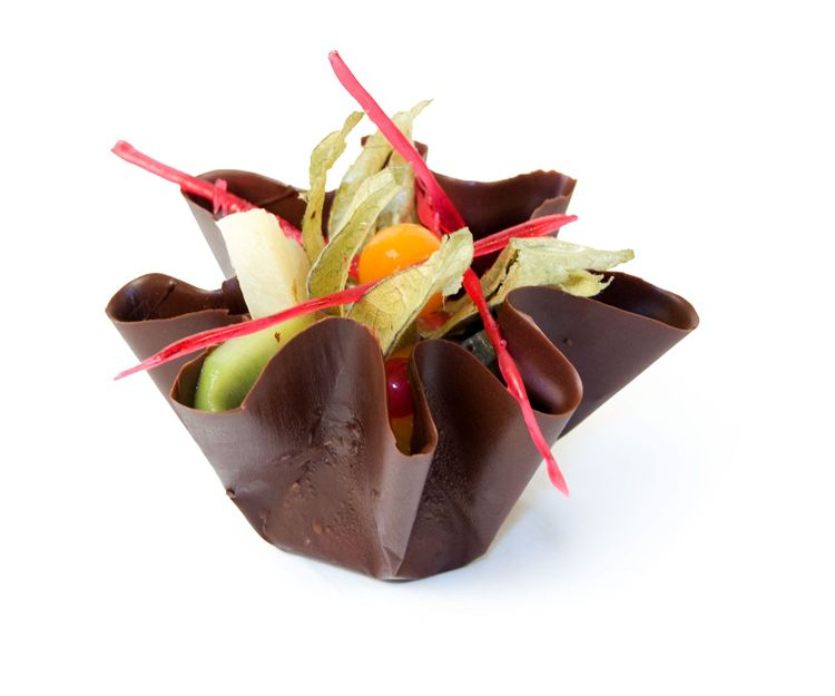 Chocolate envolviendo un pastel de helado o mousse de café o chocolate, decorado con frutas naturales
