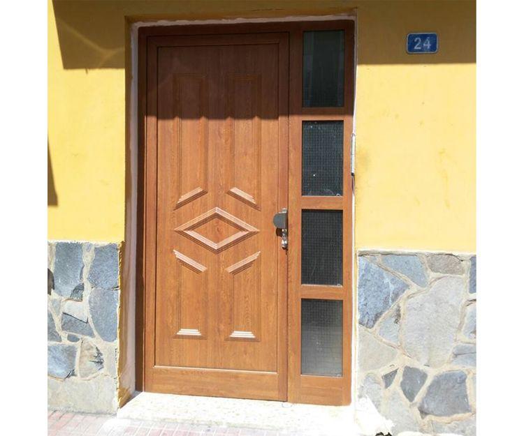 Puerta de entrada con panel ciego y un fijo con cuatro cristales