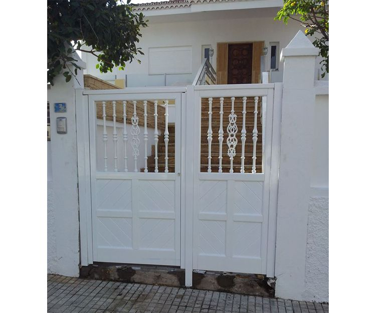 Puerta de aluminio blanca, con un fijo lateral una puerta abatible. Compuesta por travesaños, lama de machimbrado y en la parte alta balaustres