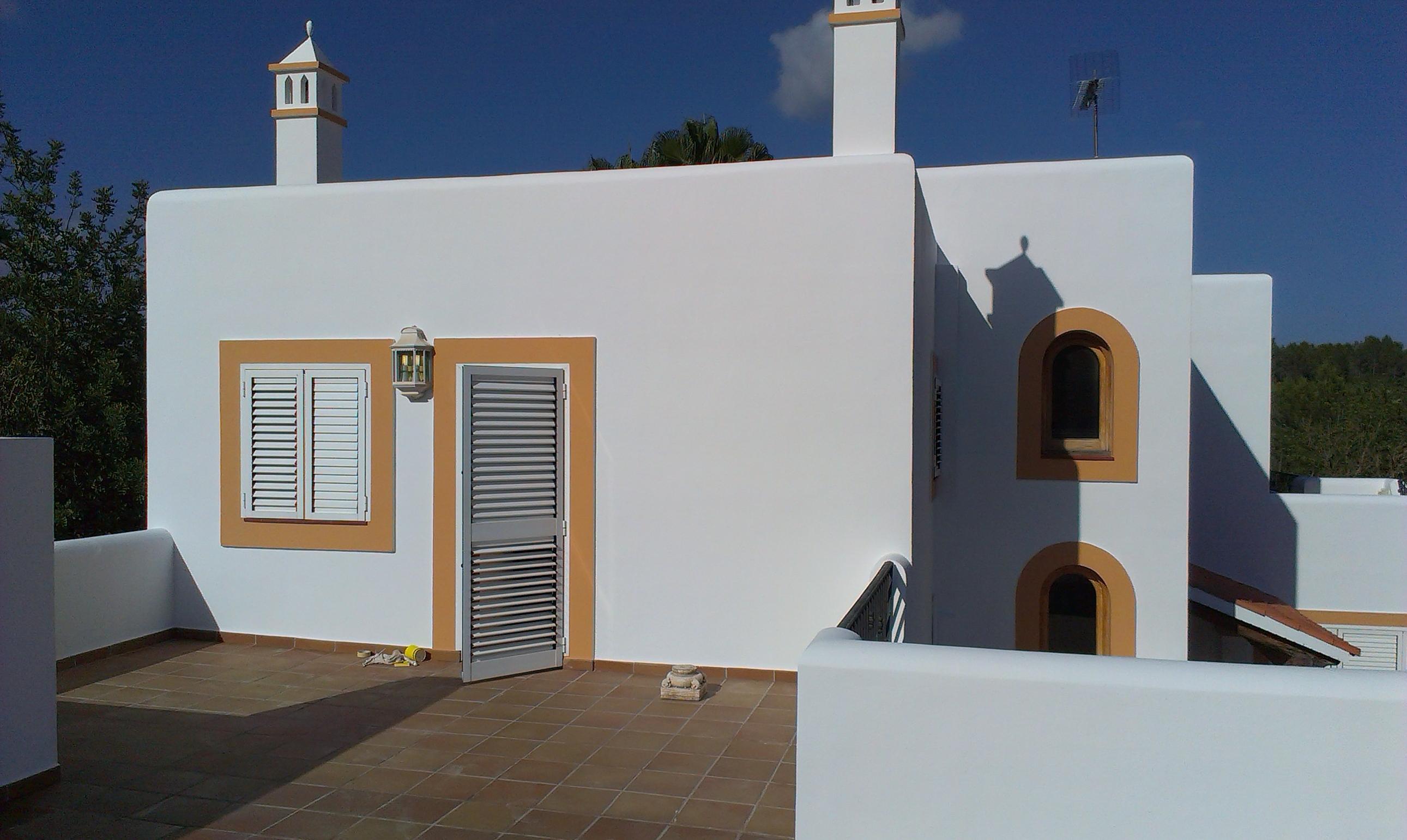 Rehabilitación de chalet  en Santa Gertrudis. Saneado de fachada con agua a presión, lucido rustico y pintura a dos colores.