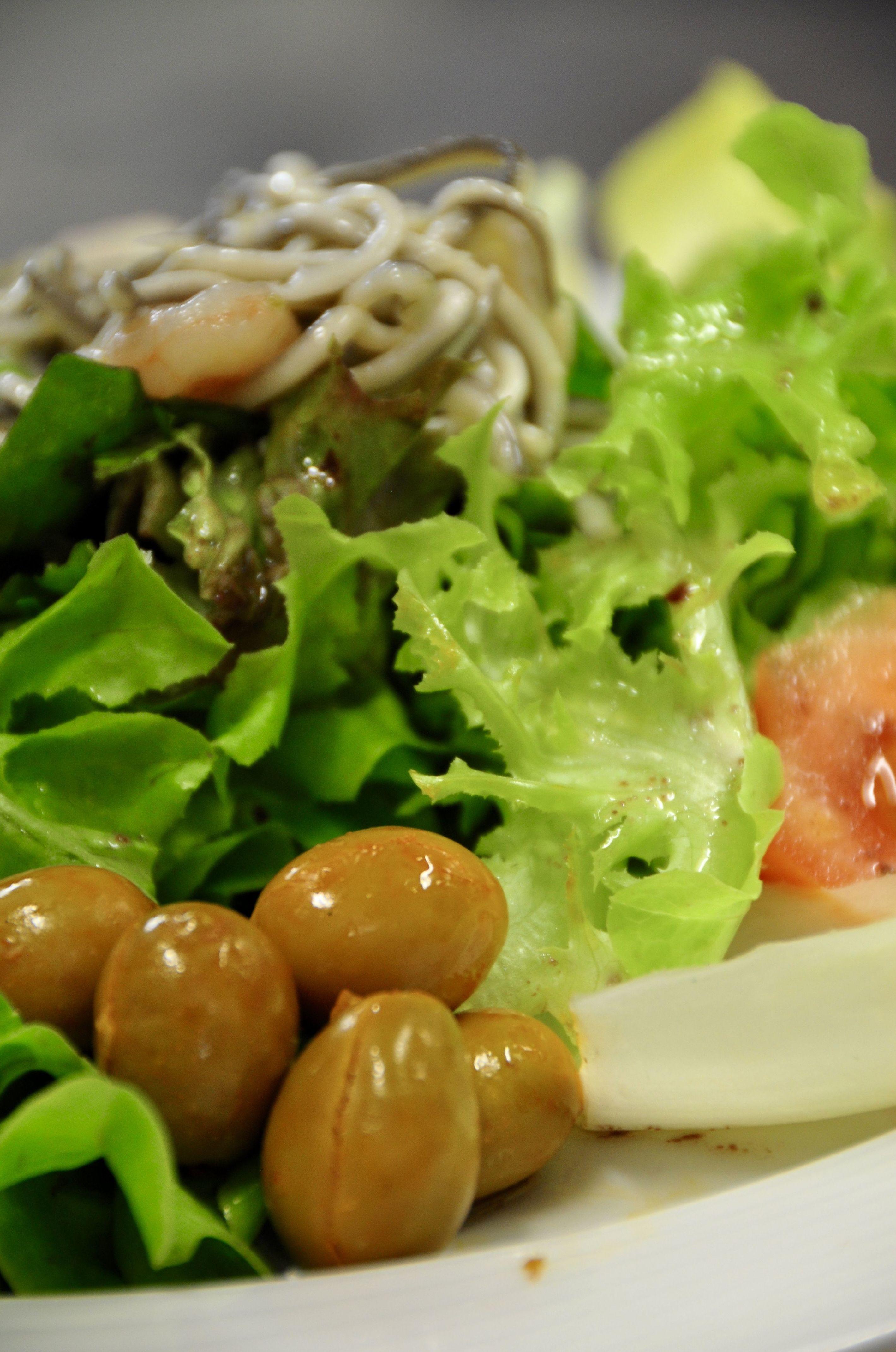 Ensalada de brotes, tomate rosa, gulas y gambas, con olivas verdes al pimentón.