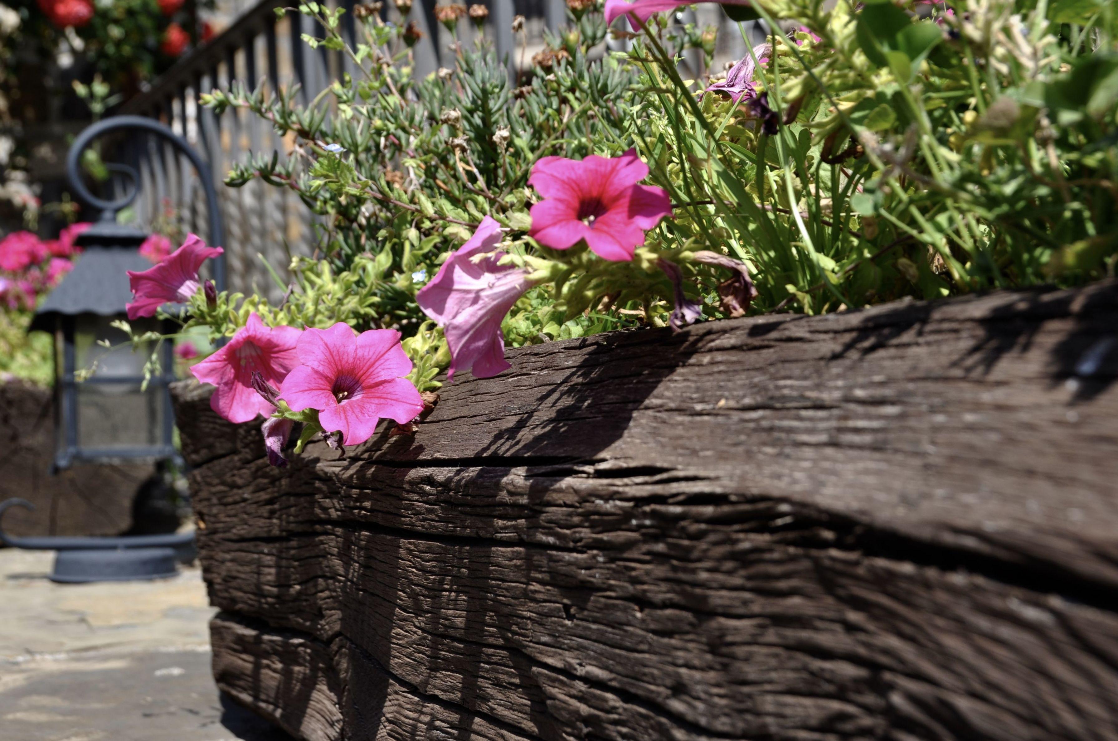 Maceteros de vigas antiguas en la terraza del Restaurante La Cocinilla.