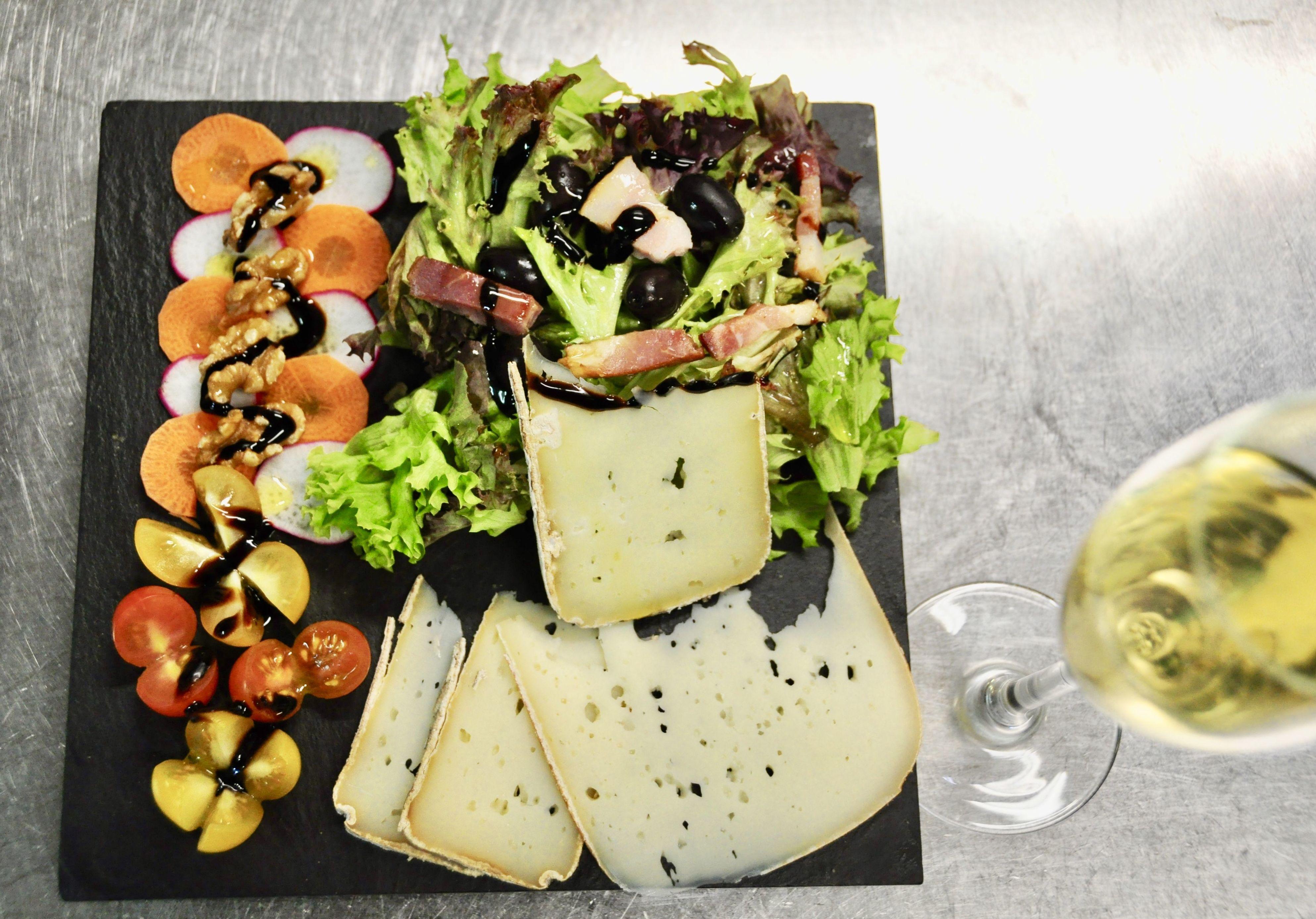 Ensalada templada de mix de quesos Bal de Broto, crujiente de beacon, frutos secos y vinagreta de miel.