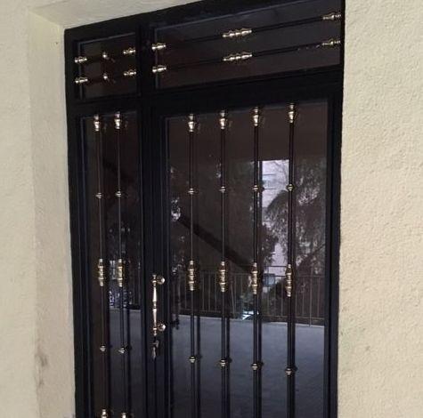 Puerta de portal con decoración de latón