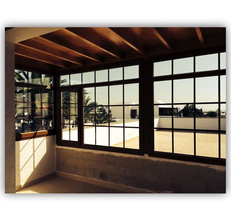 Cerramiento de terraza con ventanas, puertas y fijos con barrotillo en el interior en color roble dorado
