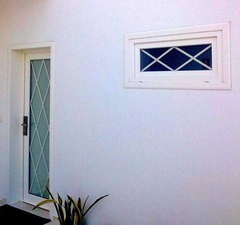 Puerta y ventana en PVC foliado blanco con cristal y barrotillo en rombo