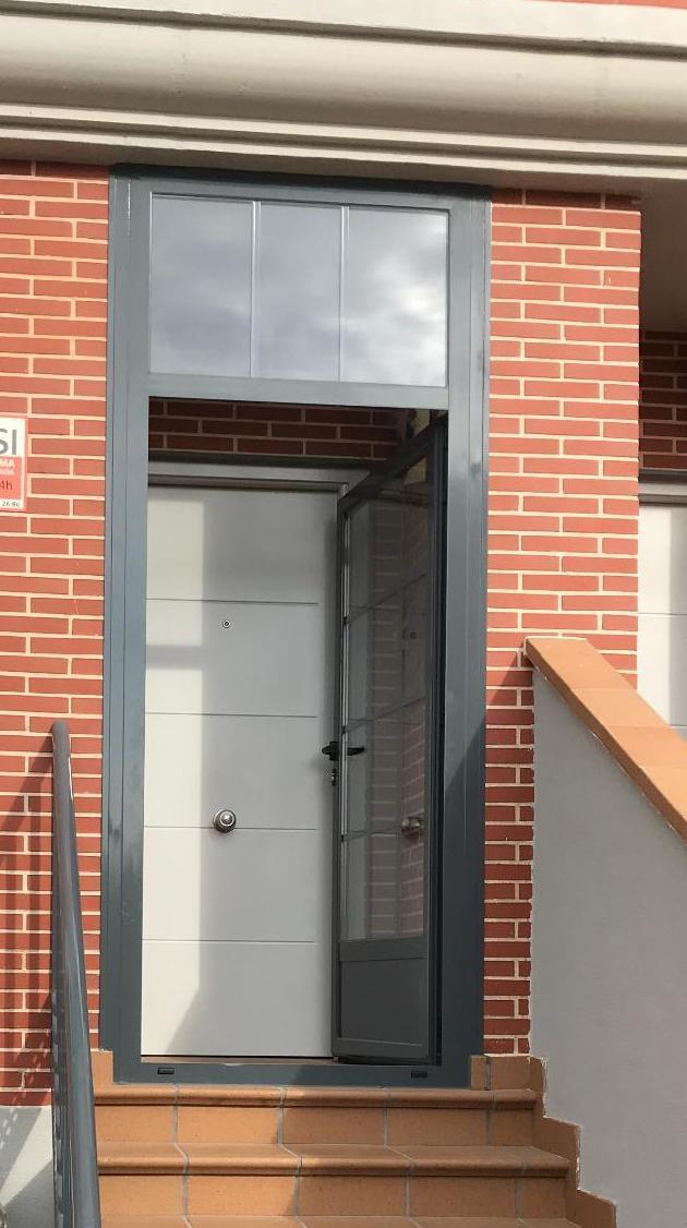 puerta para entrada en abatible de 1 hoja con fijo en la parte superior en colo ral gris , con doble acristalamiento con barrotillo ingles