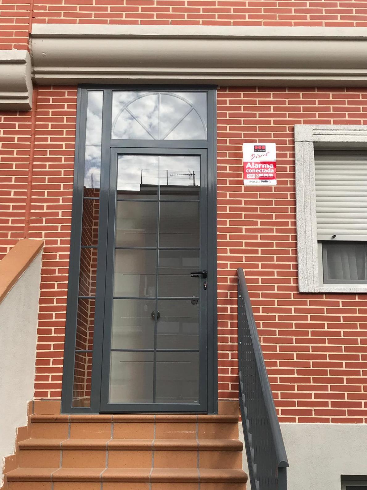 puerta para entrada en abatible de 1 hoja con fijo en la parte superior y lateral ,color ral gris , doble acristalamiento con barrotillo ingles
