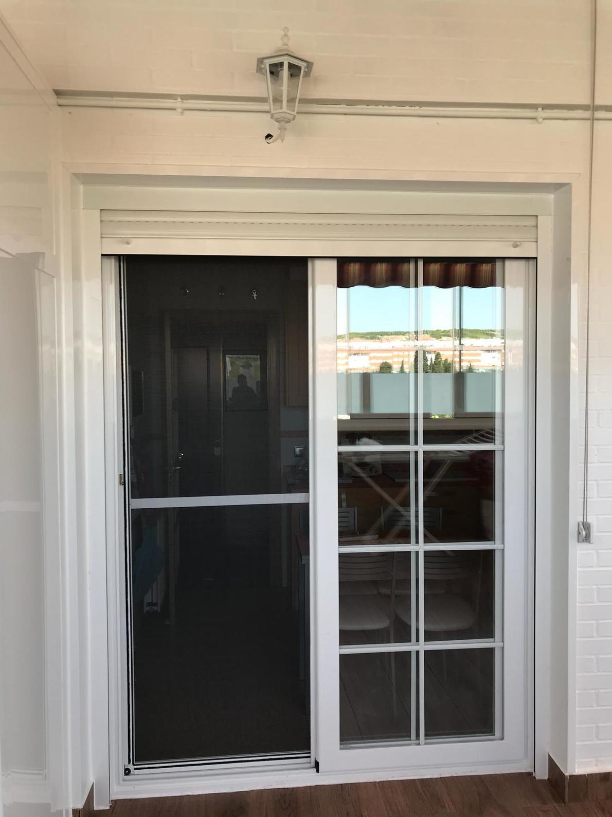 Puerta corredera de dos hojas con persiana y barrotillo ingles