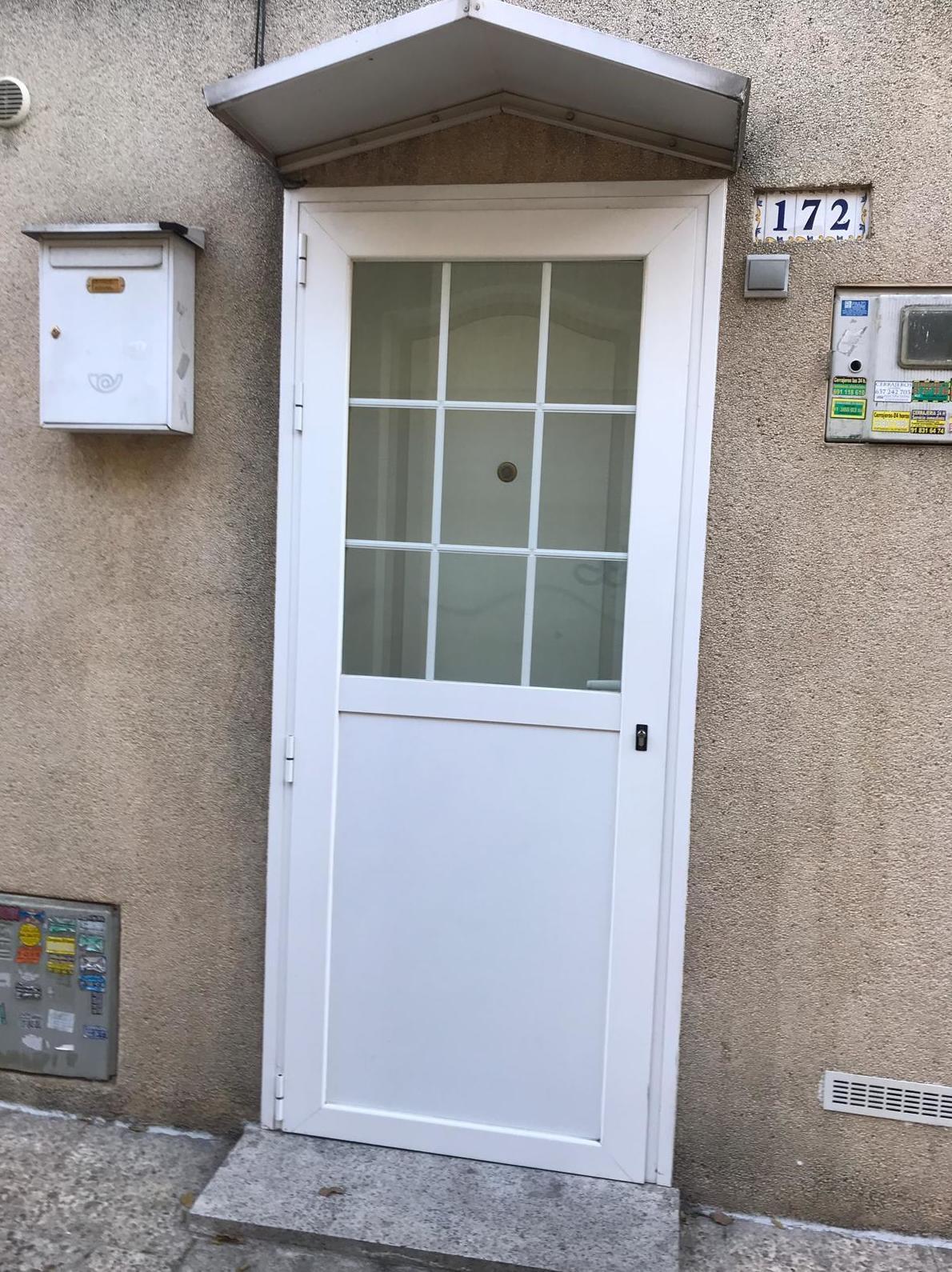 puerta abatible de 1 hoja con rotura de puente tèrmico , solapa , y doble cristal con barrotillo ingles