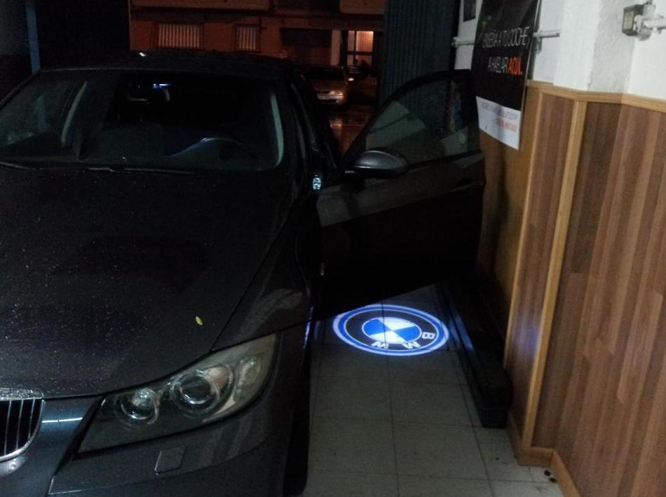 Luces en puerta con logo de la marca del coche