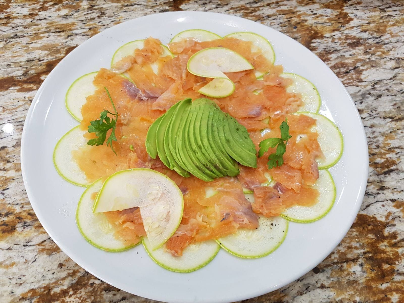 Carpaccio sabroso con salmón, aguacate, calabacín, limón y aceite