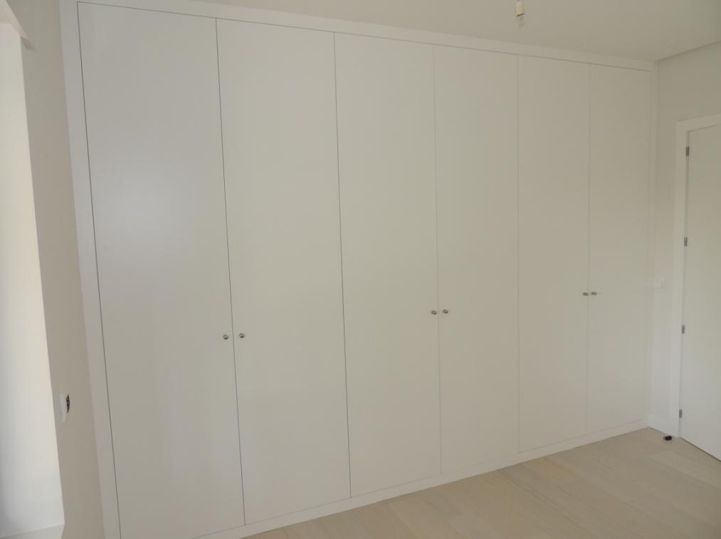 Armario de pared a pared y de suelo a techo con puertas lisas lacadas en blanco.