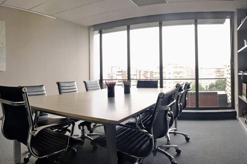 Mesa de reuniones en color Roble combinada con sillas de piel negras