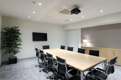 Mesa de reuniones en color Roble combinada con sillas de piel eames negras