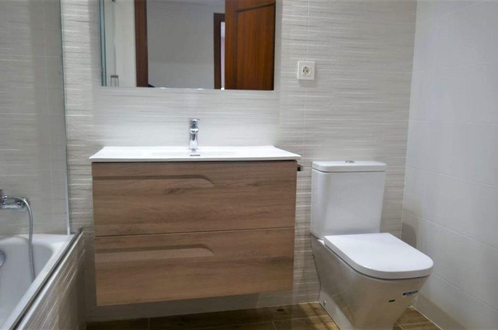 Reforma de baño en blanco con un tono de madera.