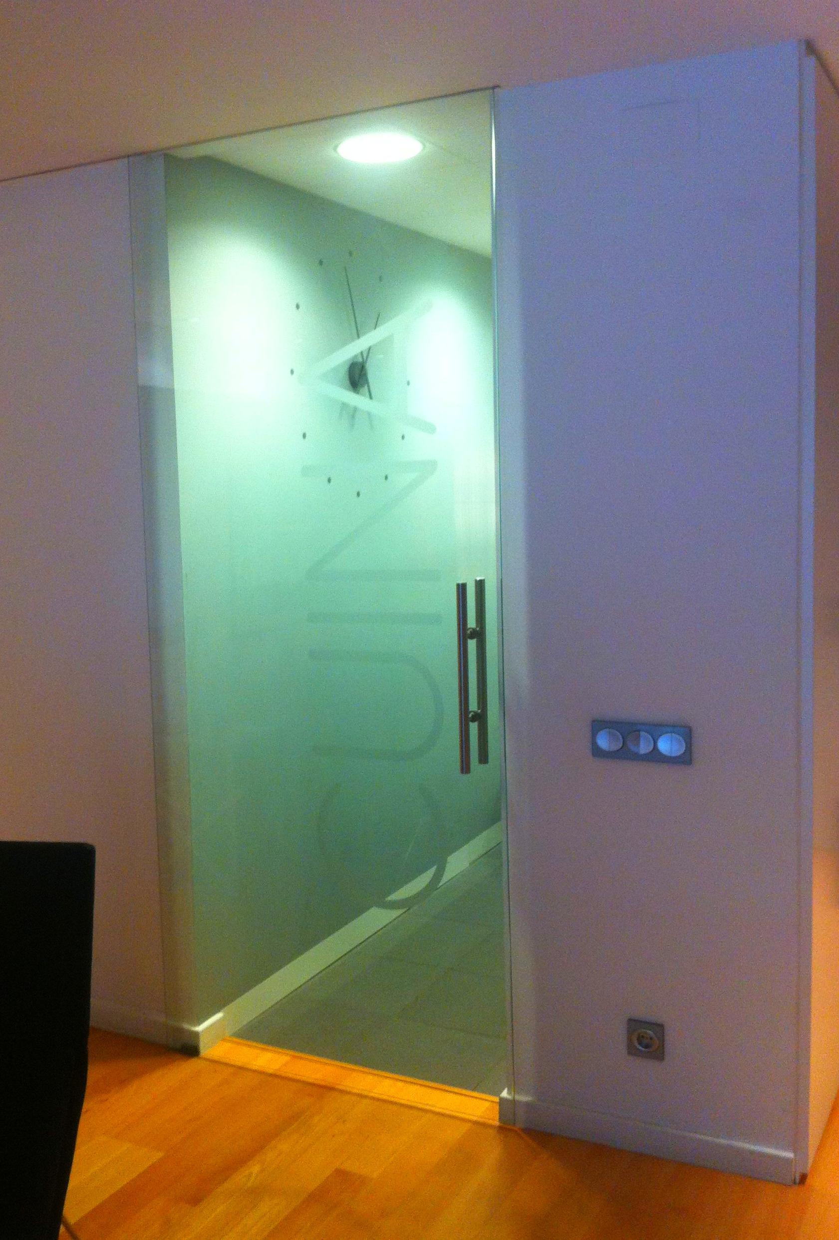 Puerta Interior de Cristal, de una hoja corredera con tirador y vinilo decorativo.