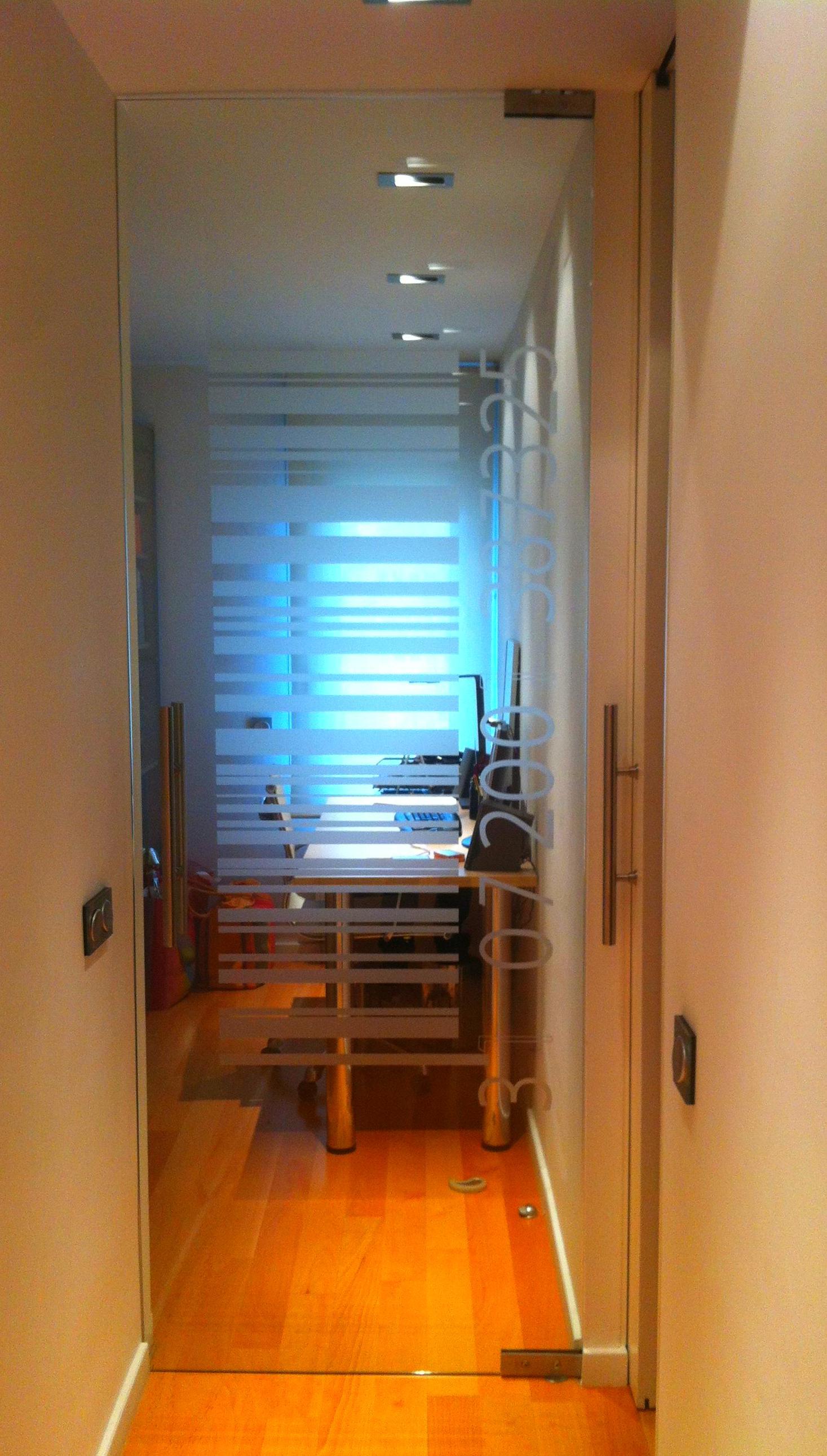 Puerta Interior de Cristal, de una hoja practicable con tirador y vinilo decorativo..