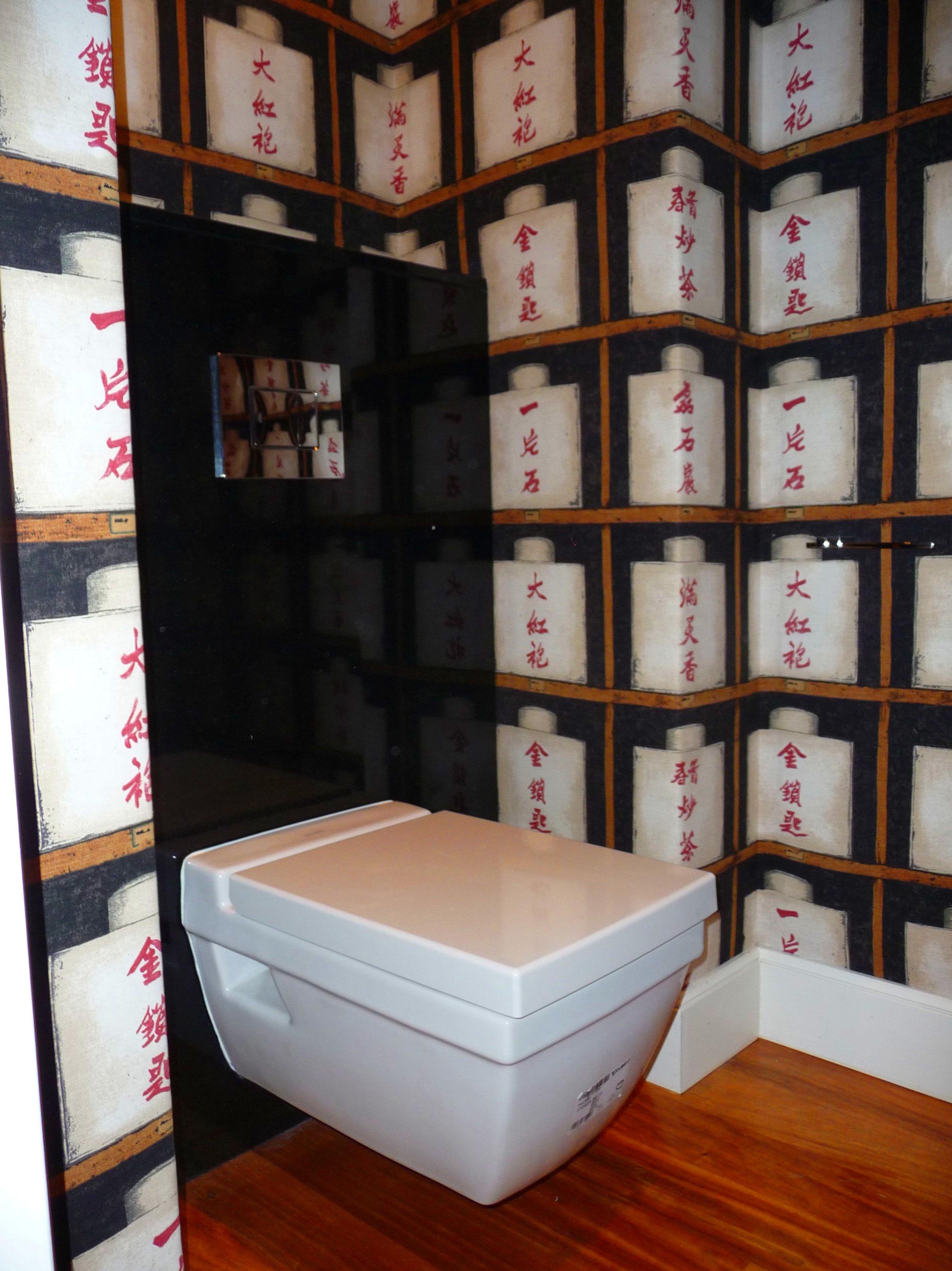 Reforma de cuarto de baño. Inodoro suspendido y paredes en papel pintado.