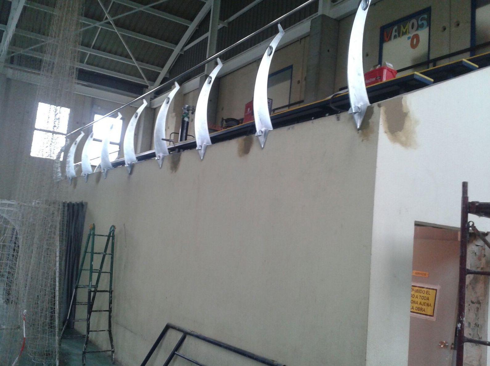 Barandilla para polideportivo con pilastars de hierro, pasamanos de inoxidable y vidrio laminado
