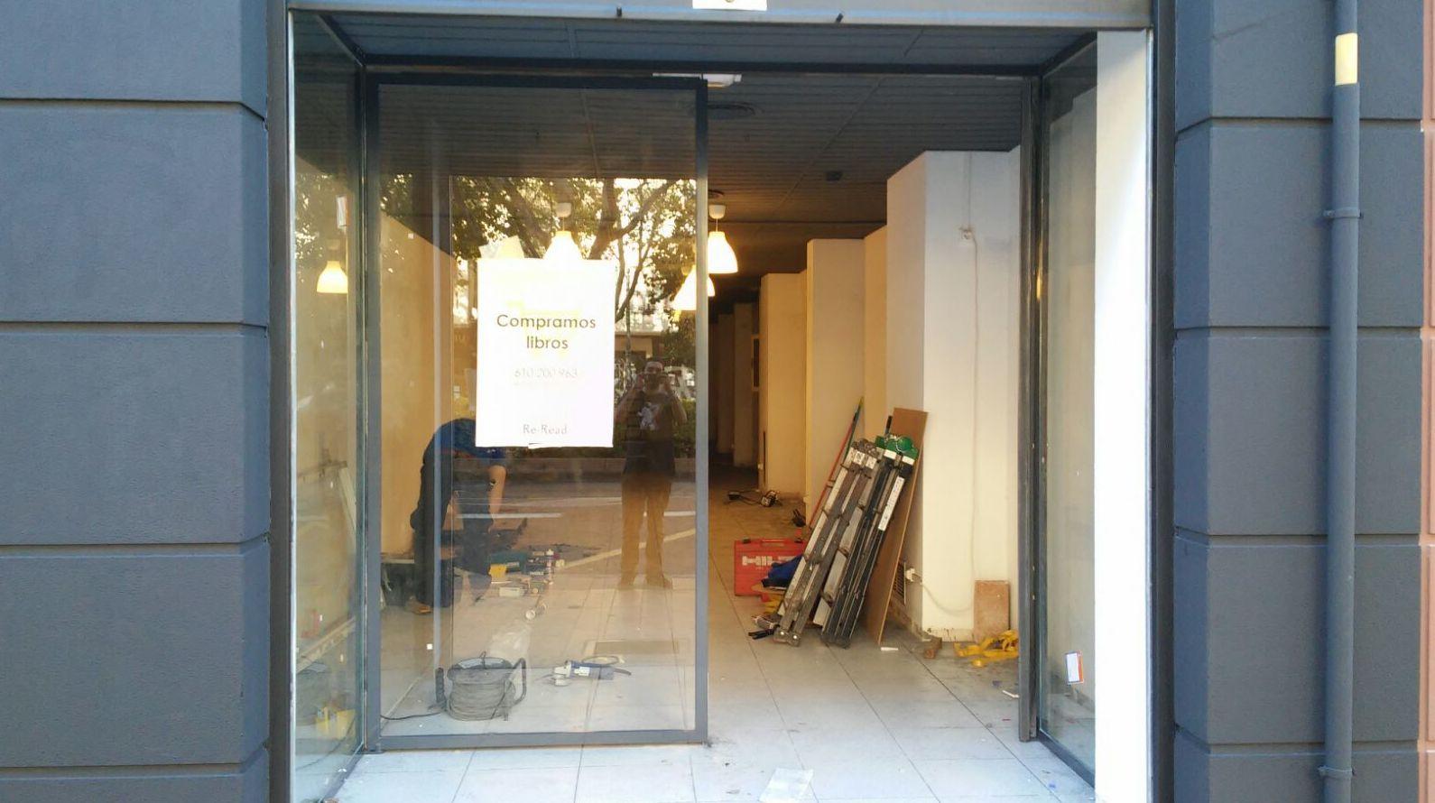 Entrada a tienda con puerta de dos hojas pivotantes de hierro lacado al horno y vidrio laminado