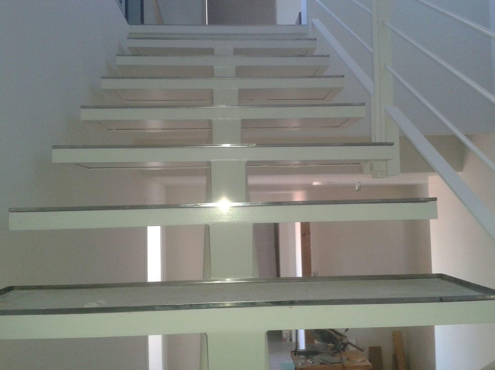 Escalera con barandilla de hierro lacado con peldaños rellenos de madera