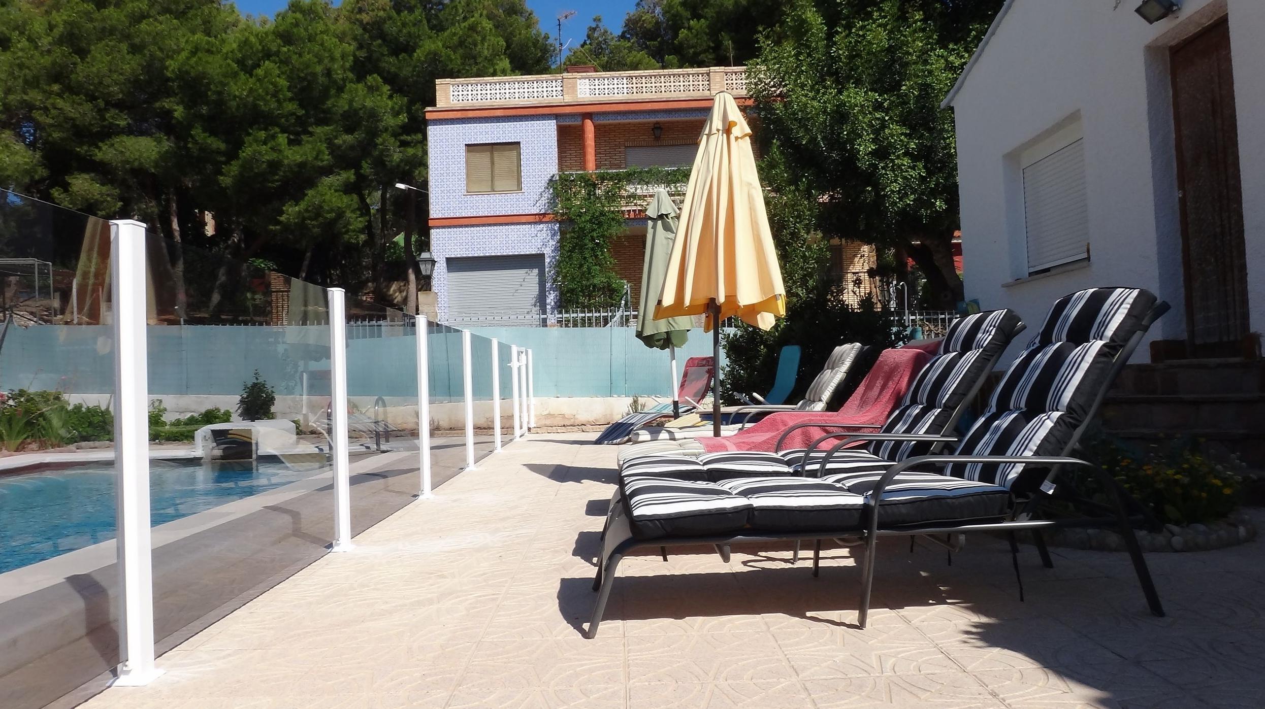 Vallado de piscina fabricado con aluminio blanco y vidrio laminado.