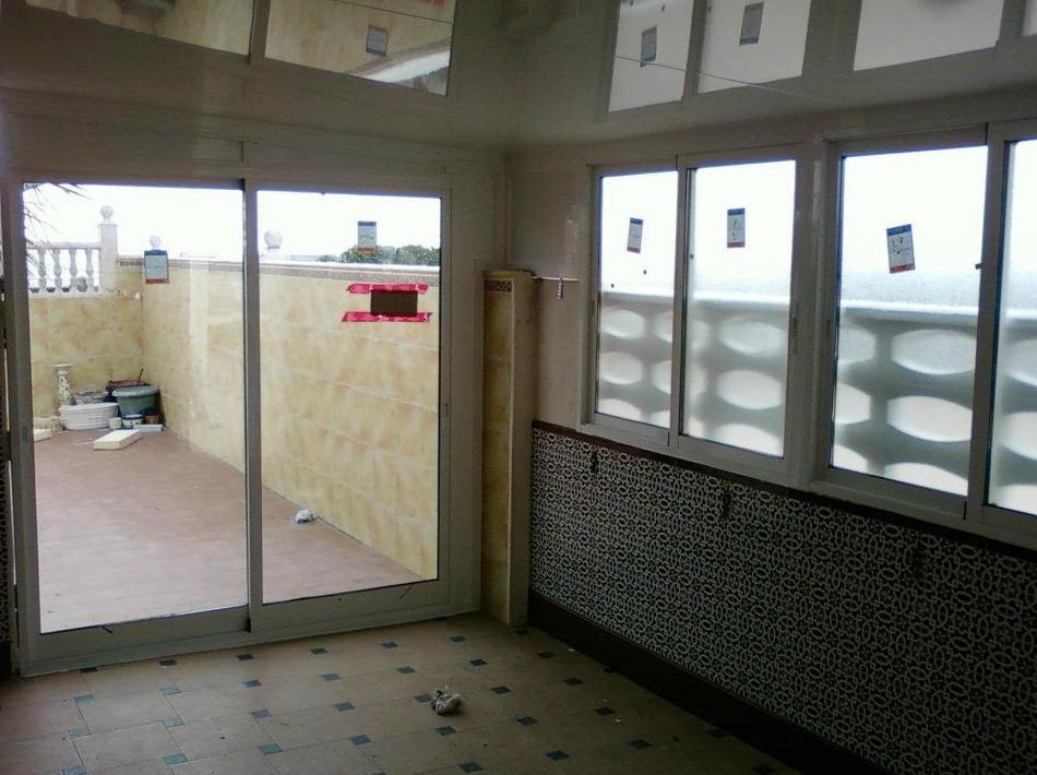 Cerramiento de terraza con techo de aluminio de panel sándwich, puerta de 2 hojas correderas y ventanas correderas (visto por dentro)