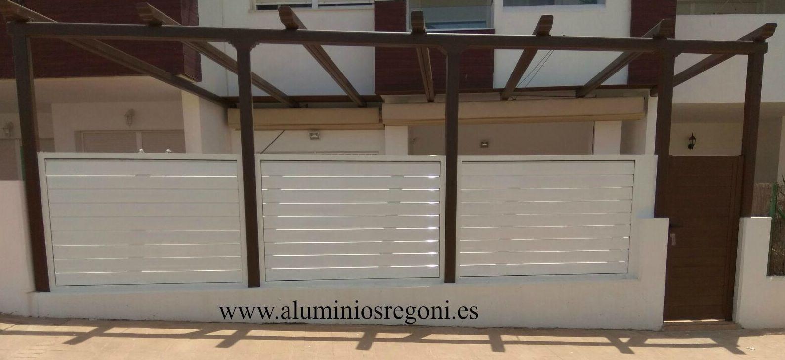 Celosia regulable de aluminio lacado blanco con puerta de aluminio imitación madera. Colocada entre pilares de toldo