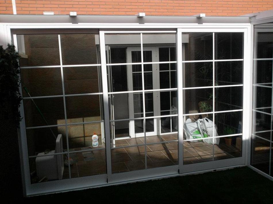 Cerramiento de terraza con techo de cristal y techo de panel sándwich y puerta corredera de 3 carriles con doble acristalamiento con palillería