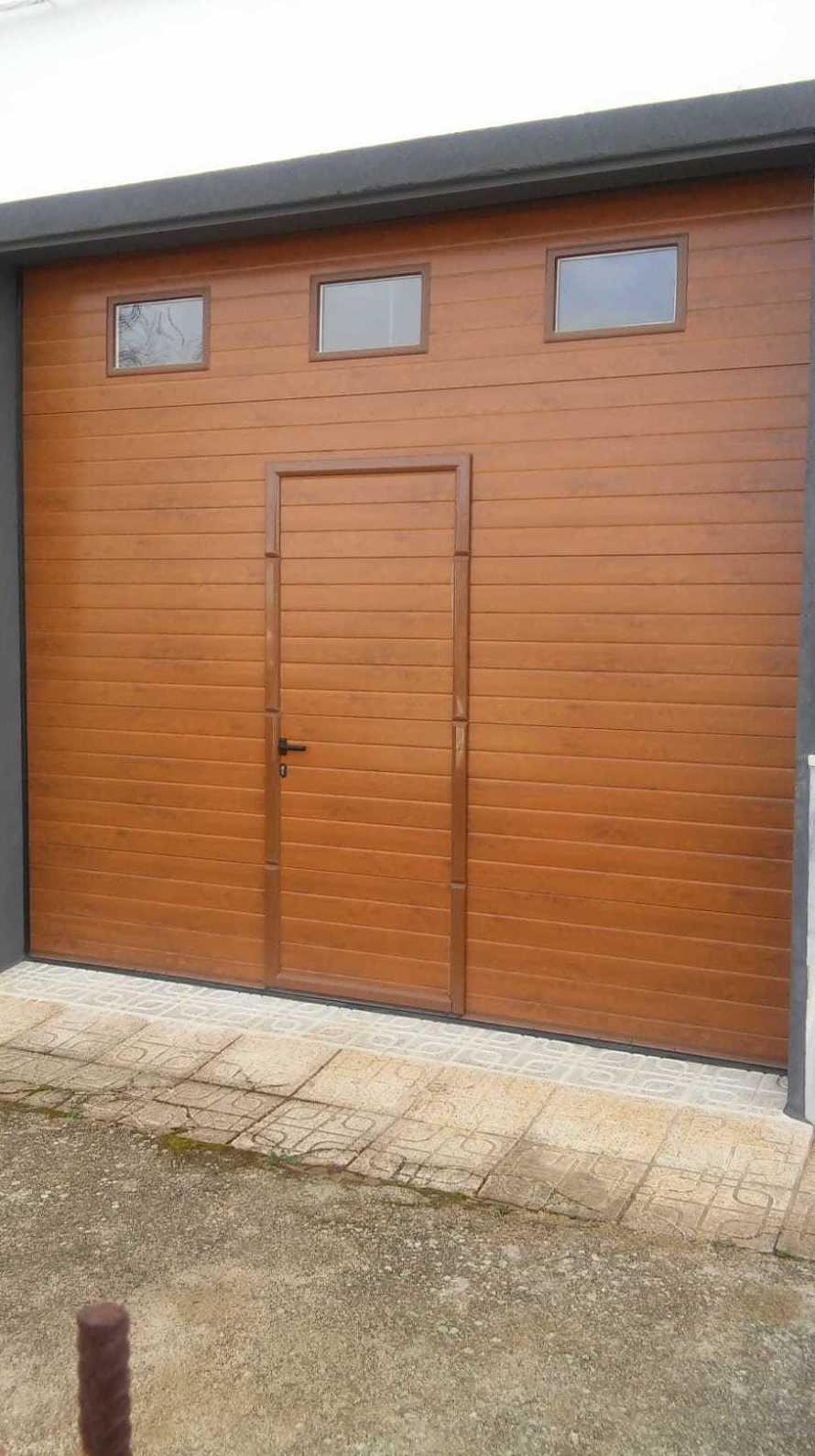 Puerta seccional imitación madera clara.