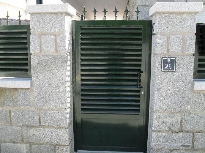 Puerta peatonal de lama ventilada con zócalo de chapa