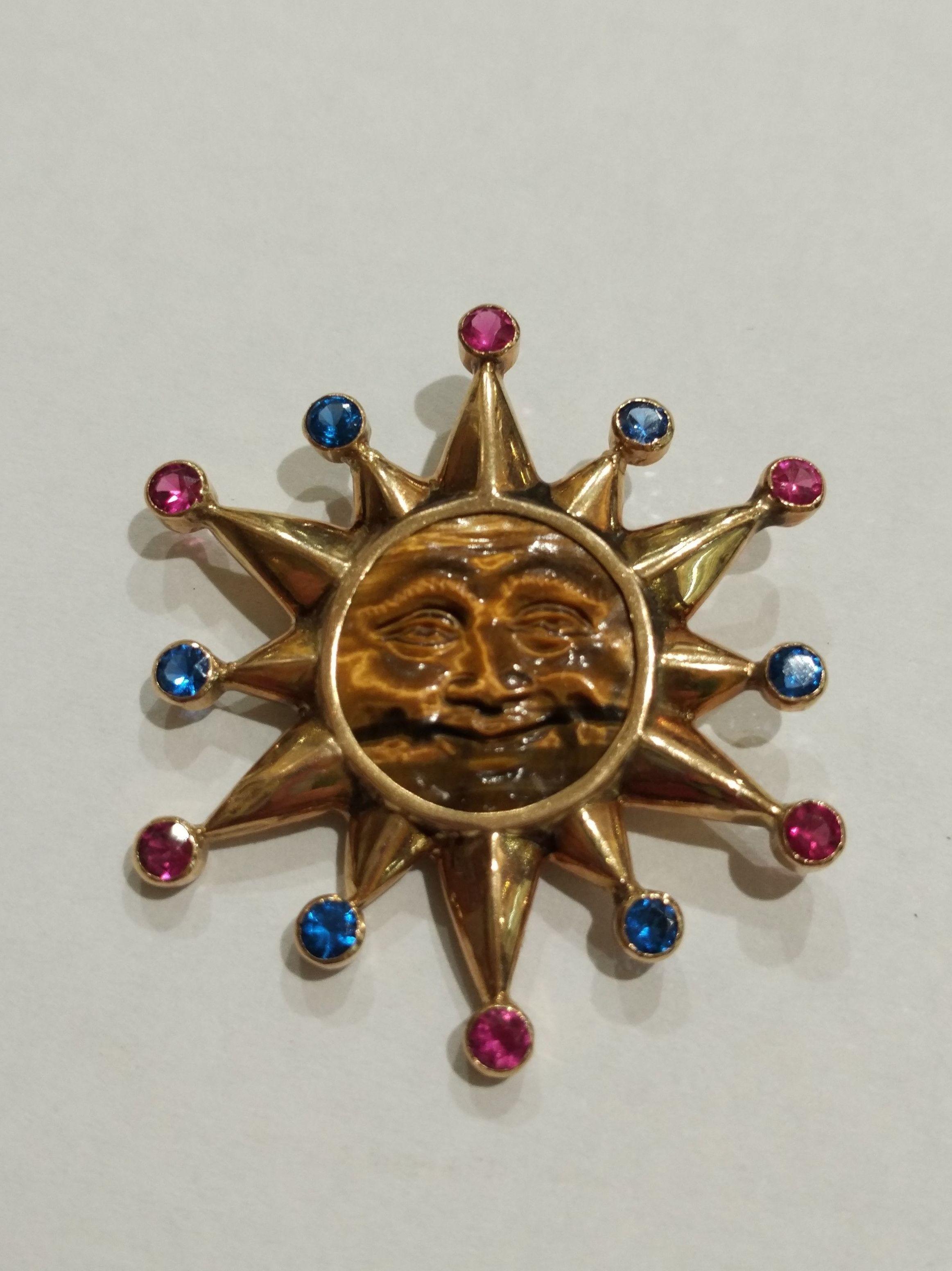 Colgante de sol en oro de 18k con ojo de tigre y vidrios. 1980.: Catálogo de Antigua Joyeros
