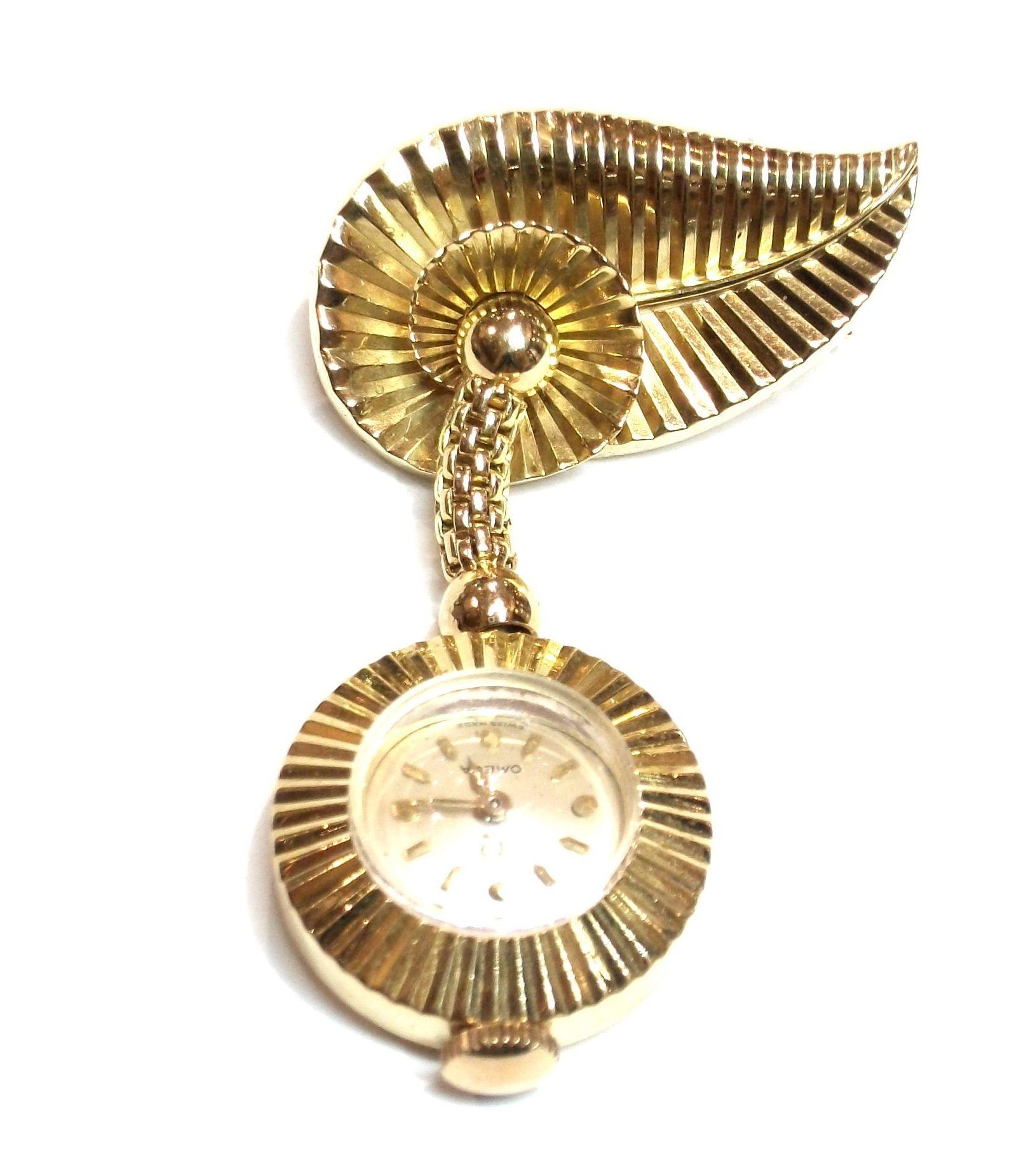 Broche con reloj colgante de marca Omega en oro 18k. 1950-60.: Catálogo de Antigua Joyeros