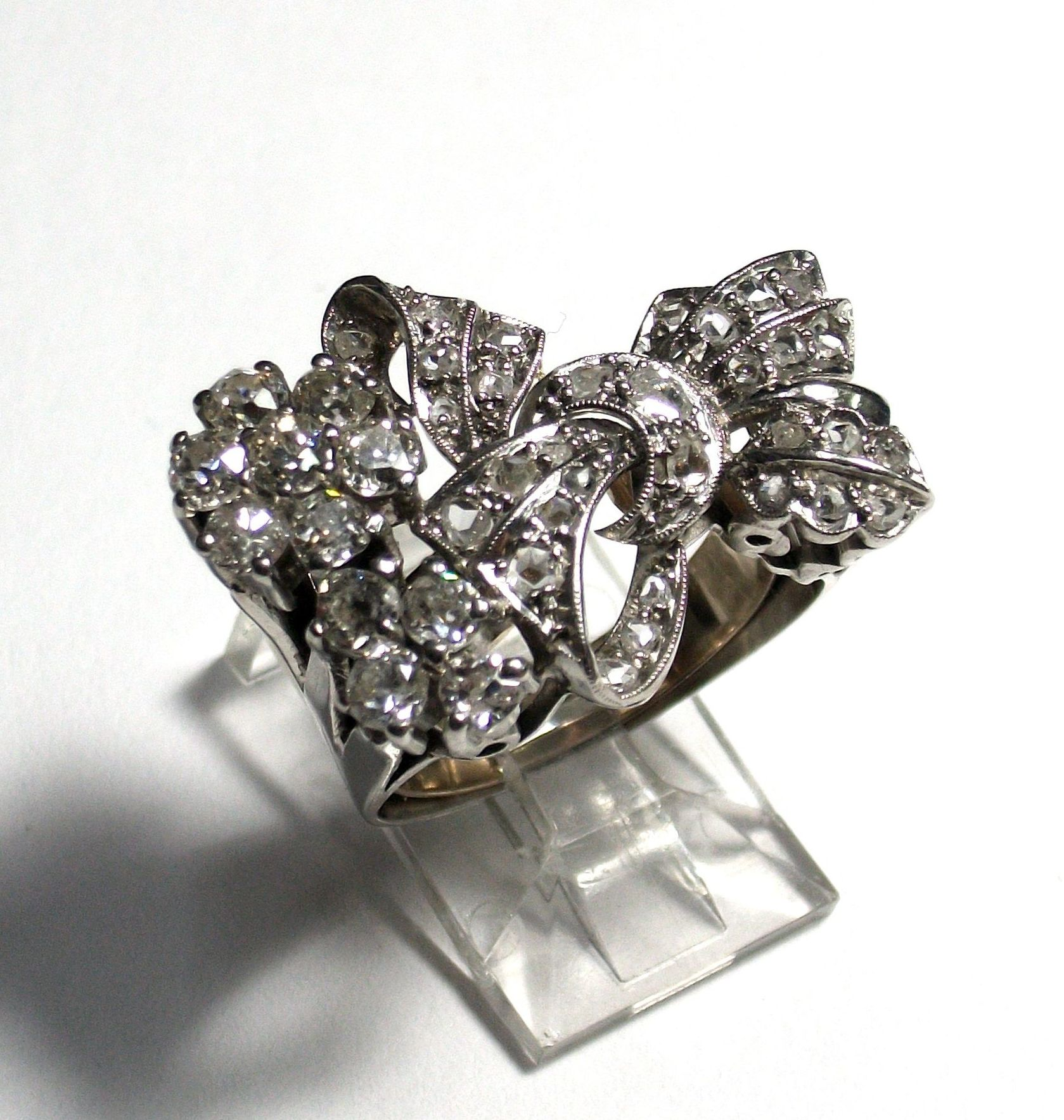Sortija de platino y diamantes con forma de lazada y flores. 1930-40.: Catálogo de Antigua Joyeros